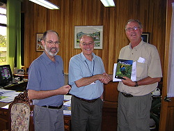 Dr. Pedro Ferreira and CATIE Board of Directors President, Dr.  Richard Rortvedt, present Thomas Wilson with a copy of Bird of the Highlands.