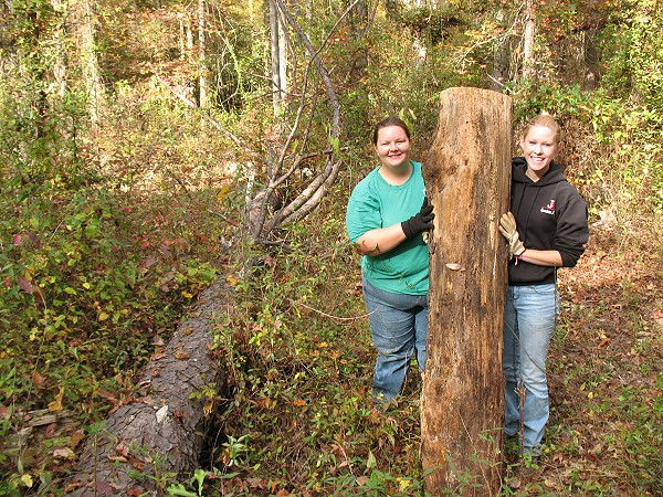 Sylvia Pitts and Samantha Marcella removing logs from trail